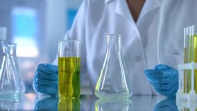 Scientist looking at test tube with yellow substance, petrol quality analysis. Stock photo stock photography