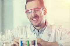 Scientist looking at test tubes with chemicals Royalty Free Stock Images