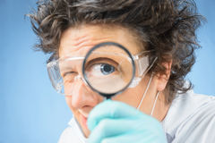 Scientist looks through a magnifying glass. Crazy man scientist looks through a magnifying glass Stock Images