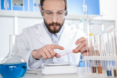 Scientist making experiment. Young male scientist in protective glasses making experiment in laboratory Stock Image
