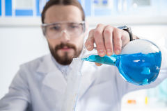 Scientist making experiment. Young male scientist in protective glasses making experiment in laboratory Royalty Free Stock Photos