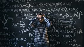 Scientist man disappointed about problems experiment in chemical and mathematical equations room. Young scientist man posing in chemical and mathematical Royalty Free Stock Photo