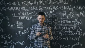 Scientist man disappointed about problems experiment in chemical and mathematical equations room. Young scientist man posing in chemical and mathematical stock video footage