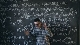 Scientist man disappointed about problems experiment in chemical and mathematical equations room. Young scientist man posing in chemical and mathematical stock footage