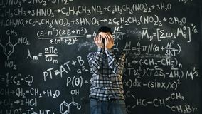 Scientist man disappointed about problems experiment in chemical and mathematical equations room. Young scientist man posing in chemical and mathematical Stock Image