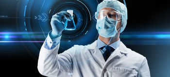 Scientist in mask holding flask with chemical Stock Photo