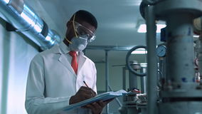 Scientist in mask writing in lab. Side view of black scientist in white lab coat, goggles and mask standing next to productional equipment with journal and stock video footage