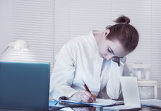 Scientist or a medic in a white coat makes notes Stock Photography