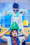 Scientists pouring liquids to big flask. Scientist men holding big flask on head white colleague pouring liquids from tubes Royalty Free Stock Photography