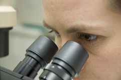 Scientist and microscope. A scientist in laboratory looks in microscope Stock Photo