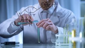 Scientist mixing substances in test tubes according to formula written on glass. Stock photo stock photo