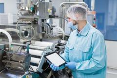 Scientist near steel machine hold empty tablet Stock Photos