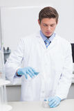 Scientist pouring chemical product in funnel Stock Photo