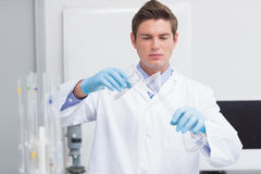 Scientist pouring chemical product in funnel. In laboratory Royalty Free Stock Images