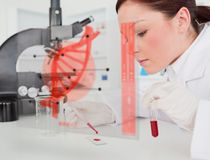 Scientist pouring drop of blood onto glass with futuristic inter Royalty Free Stock Images