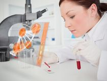 Scientist pouring drop of blood onto glass with futuristic interface Royalty Free Stock Photos