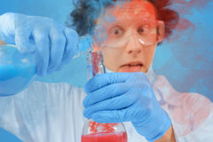 Scientist is pouring liquid into flask Stock Photos