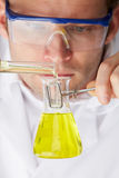 Scientist Pouring Liquid From Test Tube Into Flask. With Goggles On Royalty Free Stock Images