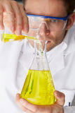 Scientist Pouring Liquid From Test Tube Into Flask Royalty Free Stock Photo