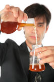 Scientist pours liquid from flask in another Royalty Free Stock Images