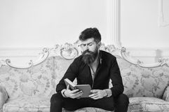 Scientist, professor on thoughtful face enjoy literature. Lecturer sit on sofa and reading book, white wall background. Man with beard and mustache spends stock photography