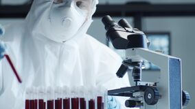 Scientist in protection suit and masks working in research lab using laboratory equipment: microscopes, test tubes