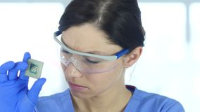 Scientist in protective glasses looking at computer chip. 4k, high quality stock video footage