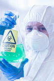 Scientist in protective suit with hazardous chemical in flask Stock Images