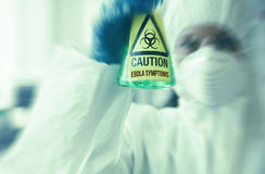 Scientist in protective suit holding beaker Royalty Free Stock Image