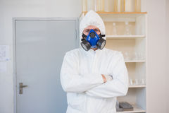 Scientist in protective suit looking at camera with arms crossed Stock Photo