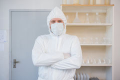 Scientist in protective suit looking at camera with arms crossed Stock Image