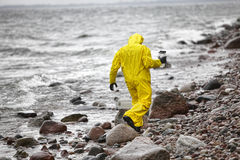 Scientist in protective suit with plastic container walking in on rocky beach Royalty Free Stock Photos