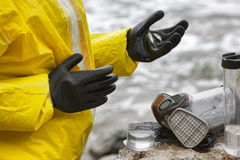 Scientist in protective uniform examining little fishes on hand in glove Royalty Free Stock Photos