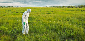 Scientist in protective uniform on summer field Royalty Free Stock Photos
