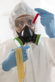 Scientist in protective wear with blood sample Stock Image