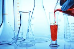 Scientist's hand pouring chemical liquid Stock Photos