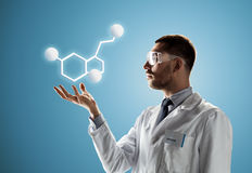 Scientist in safety glasses with molecular formula. Science, chemistry, biology, medicine and people concept - male doctor or scientist in white coat and safety Stock Image