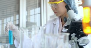 Scientist shake liquid in test tube for experiment. Scientist shaking blue liquid in test tube for experiment in laboratory room stock footage