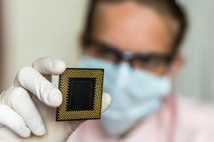 Scientist showing the computer microchip before repairs electron Stock Photos