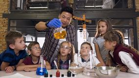 Scientist showing kids how to do chemical reaction experiments in lab class. Chemical reaction orange color in glasses stock footage