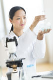 Scientist Smiling While Analyzing Chemical Solution Stock Photos
