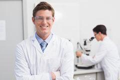 Scientist smiling at camera arms crossed and another working with microscope. In laboratory Stock Image