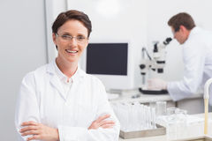 Scientist smiling at camera arms crossed and another working with microscope Stock Photos