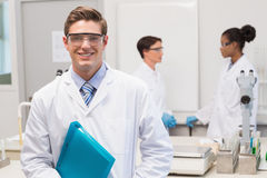 Scientist smiling at camera while colleagues talking together. In the laboratory Stock Image