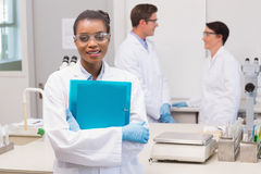 Scientist smiling at camera while colleagues talking together. In the laboratory Royalty Free Stock Photography