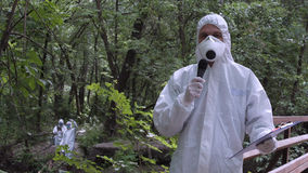 Scientist speaking microphone in woods. Man wearing protective suit holding file in hands and speaking microphone while looking at camera on nature Royalty Free Stock Image