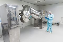 Scientist stand check readings about machine with rolling barrels. Caucasian scientist in blue lab suit and gloves check readings of big steel machine with Royalty Free Stock Image