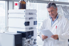 Scientist standing in lab coat reading analysis Royalty Free Stock Image