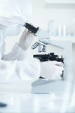 Scientist in sterile environment with microscope. Selective focus stock photos