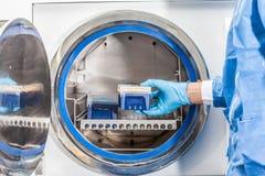 Scientist sterilizing laboratory material Royalty Free Stock Photos
